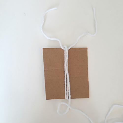 Für eine Quaste wird ein Stück Karton umwickelt
