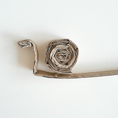 Schnecken aus Karton, aus einem Kartonstreifen wurde ein Schneckenhaus gewickelt, wie auch ein Kopf und Körper diese einzelen Teile liegen auf einem weißen Untergrund
