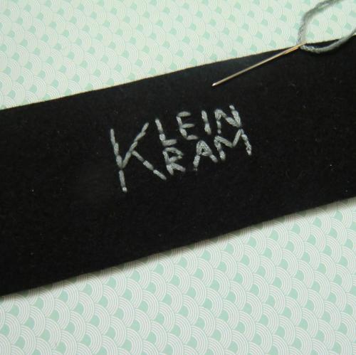 ein schwarzer Filz auf welchem mit grauem Garn KLeinkram gestickt ist, auch ist eine Nadel zu sehen