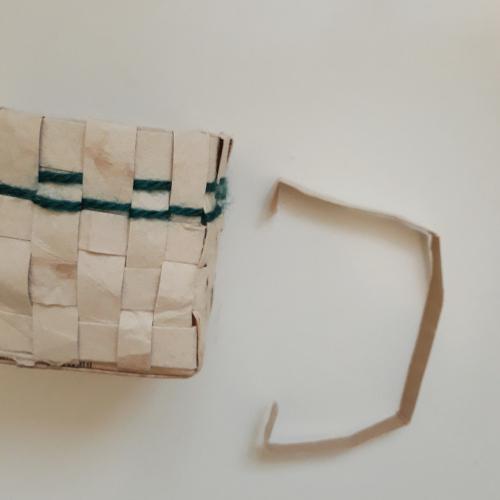 zu sehen ist ein Flechtkorb aus einem upgecycelten Tetrapack. Auch wurde hier noch grüne Wolle eingewoben, daneben liegt ein Streifen, der ebenfalls aus einem Tetrapack ausgeschnitten wurde. Dieser wird der Henkel des Osterkörbchens