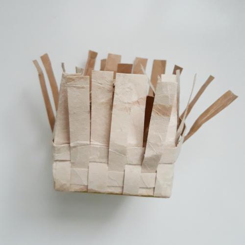 zu sehen ist der Boden eines Tetrapacks, es werden die zuerst geschnittenen Streifen eingewoben damit ein Korb entsteht