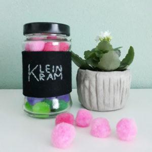 Schraubglas für Kleinkram, Upcycling eines Schraubglases, Im Glas befinden sich grüne und rosane PomPoms, daneben steht eine Pflanze, welche weiß blüht in einem Beton-Übertopf