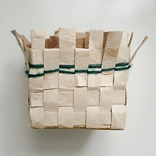 Zu sehen ist ein gewebter Korb aus Tetrapack, es wurde auch eine grüne Wolle eingewoben