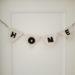 PunchNeedele Wimpelkette hängt an einer Tür, Selbstgemachte Wimpelkette mit weißem Stoff und schwarz gepunshten Buchstaben, HOME ist auf die Girlande gestickt