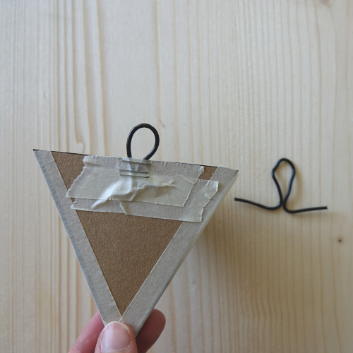 Geometrischer Wandblumentopf, die Aufhängung aus Draht wird gebogen